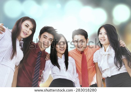 Group of business team smiling at the camera, shot against light glitter background