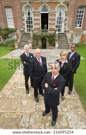 Group of businessmen and woman by manor house, portrait, elevated view