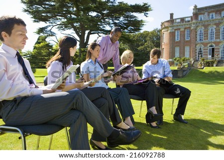 Group of businessmen and women in training course outdoors by manor house