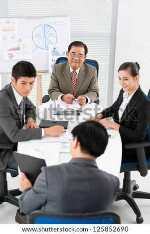 Group of businessmen sitting and looking at colleague - stock photo