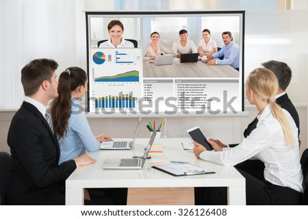 Group Of Businesspeople Attending Video Conference In Office - stock photo