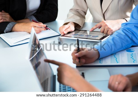 Group of businesspeople busy discussing financial matter during meeting - stock photo