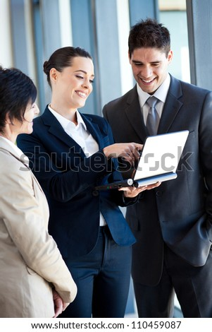 group of businesspeople discussing business on laptop