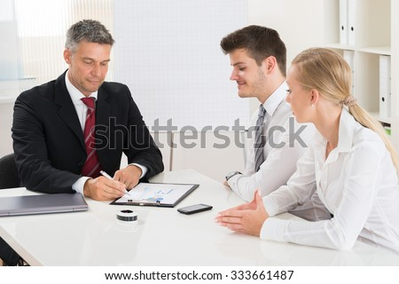 Group Of Businesspeople Discussing On Graph At Desk