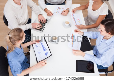 Group Of Businesspeople Discussing On Graph In Meeting - stock photo