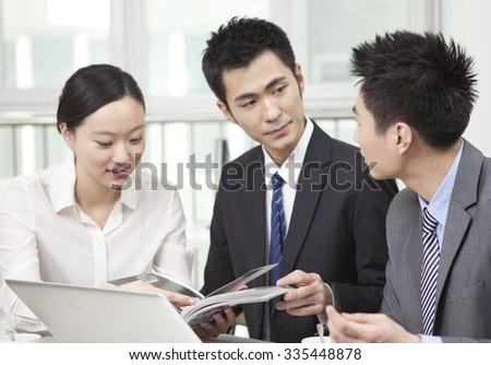 Group of businesspeople discussing with a magazine in office