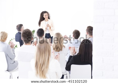 Group of businesspeople during company's meeting congratulating young successful woman leadership - stock photo
