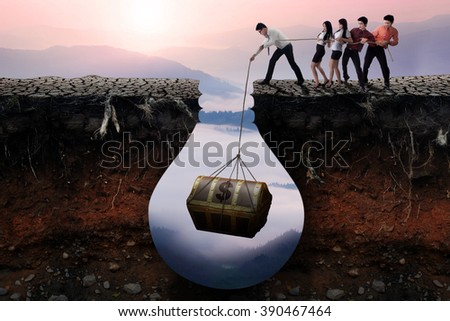 Group of businesspeople finding a treasure chest in the soil and try to get it together - stock photo