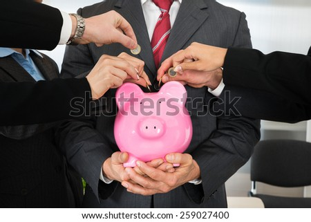 Group Of Businesspeople Hands Inserting Coin In Piggybank