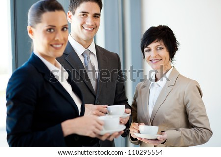 group of businesspeople having coffee during break in office - stock photo