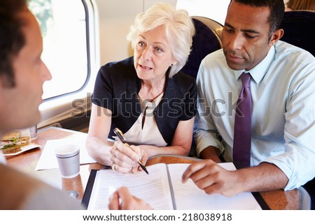 Group Of Businesspeople Having Meeting On Train