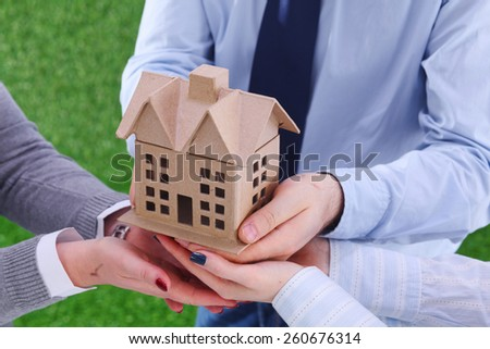 Group of businesspeople holding model house - stock photo