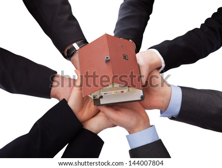 Group Of Businesspeople Holding Model House Over White Background - stock photo