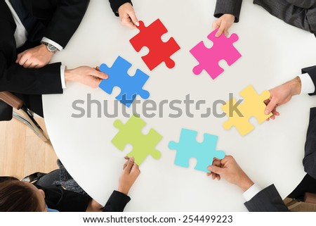 Group Of Businesspeople Holding Multi-colored Jigsaw Puzzle Sitting At The Table