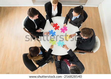 Group Of Businesspeople Holding Multi-colored Jigsaw Puzzle Sitting At The Table - stock photo