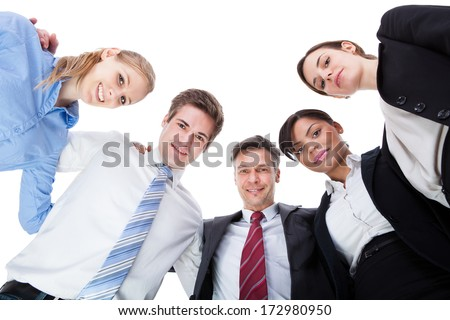 Group Of Businesspeople In A Circle Looking Down Over White Background