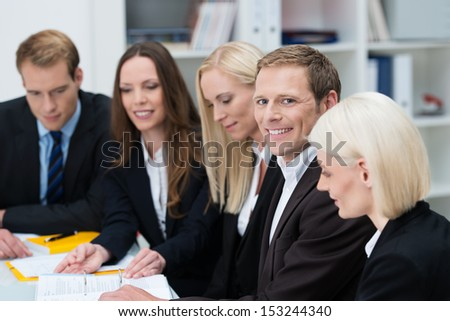 Group of businesspeople in a meeting seated at a table with focus to a smiling confident man in the centre of the group - stock photo