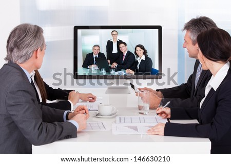 Group Of Businesspeople In Video Conference At Business Meeting - stock photo