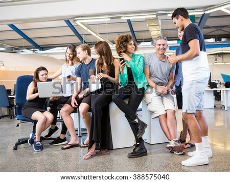 Group of businesspeople interacting during break time in office - stock photo