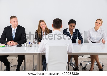 Group Of Businesspeople Interviewing Man In Office