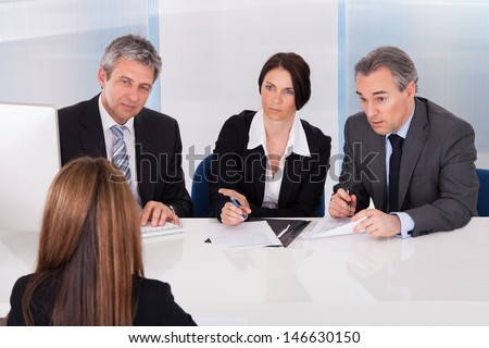 Group Of Businesspeople Interviewing Woman In Office - stock photo
