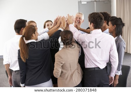 Group Of Businesspeople Joining Hands In Circle At Company Seminar