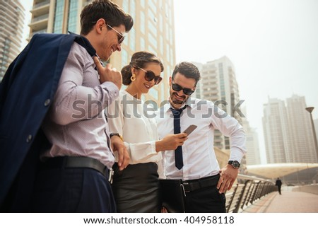 Group of businesspeople looking at mobile phone. - stock photo