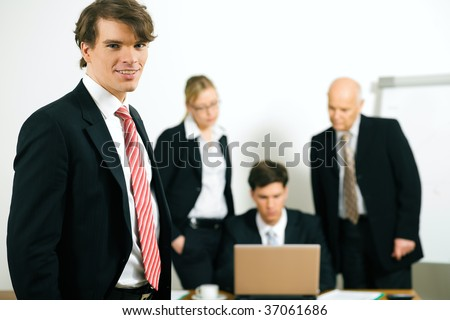 Group of businesspeople, one standing in the front, three more working in the background - stock photo