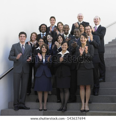 Group of businesspeople standing on stairs clapping