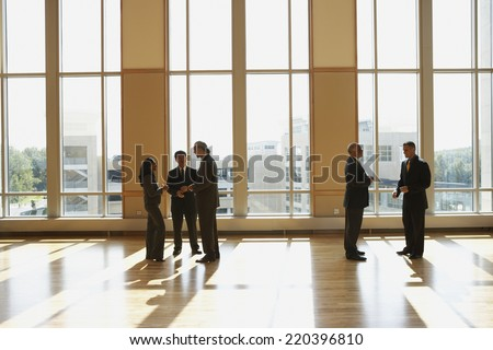 Group of businesspeople talking in sunlit room - stock photo