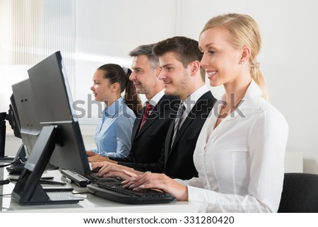 Group Of Businesspeople Typing On Desktop Computer At Desk