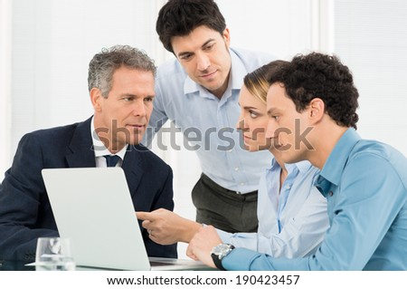 Group Of Businesspeople Using Laptop In Meeting