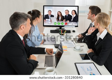 Group Of Businesspeople Watching An Online Presentation On A Desktop Computer In Office