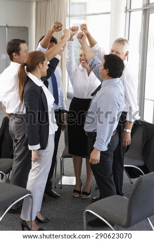 Group Of Businesspeople With Arms Raised At Company Seminar - stock photo