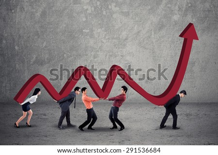 Group of businesspeople work together to carry a business graph with upward arrow