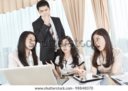 Group of businesswomen having discussion with a manager watching from behind - stock photo
