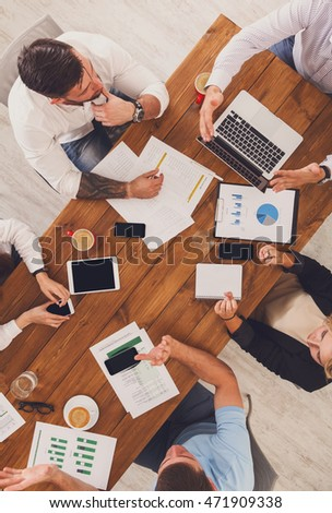 Group of busy business people working in office, top view of wooden table with mobile phones, laptop, tablet and documents papers with diagram. Men and women team have brainstorm discussion, vertical