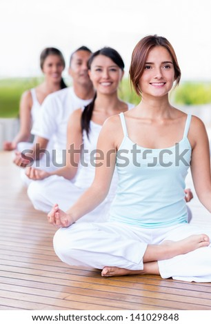 Group of calm people doing yoga and looking peaceful - stock photo