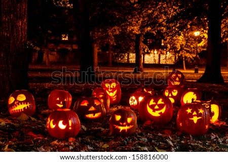Group of candle lit Halloween pumpkins in park on fall evening - stock photo