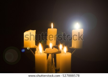 Group of candles glowing in darkened room