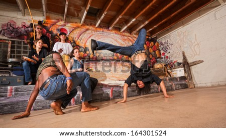 Group of capoeira performers in urban building doing flips - stock photo