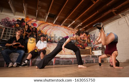 Group of capoeira performers with music in urban building - stock photo