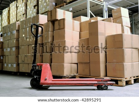Group of carton boxes and fork pallet truck stacker in warehouse in front of cardboard boxes - stock photo