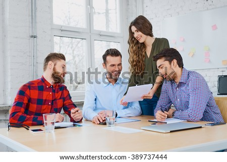 Group of casual business partners working together in modern office