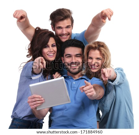 group of casual friends reading on a tablet pad computer and point fingers to the camera