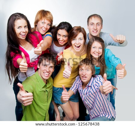 group of casual happy people smiling and shows fingers at the camera