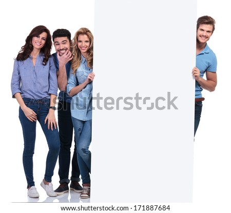 group of casual people fooling around and presenting a blank board on white background - stock photo