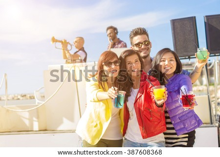 Group of caucasian people are celebrating raising their cocktails at a beach party - stock photo