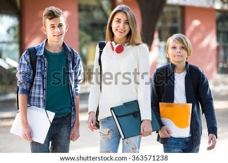 Group of caucasian teens going to school with papers for study  - stock photo
