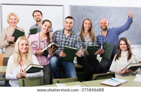 Group of cheerful adult students and coach posing at training session school. Selective focus - stock photo